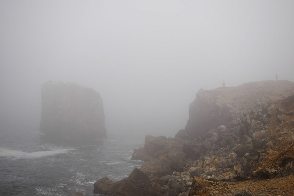 People fishing in the fog on the cliffs of Peniche